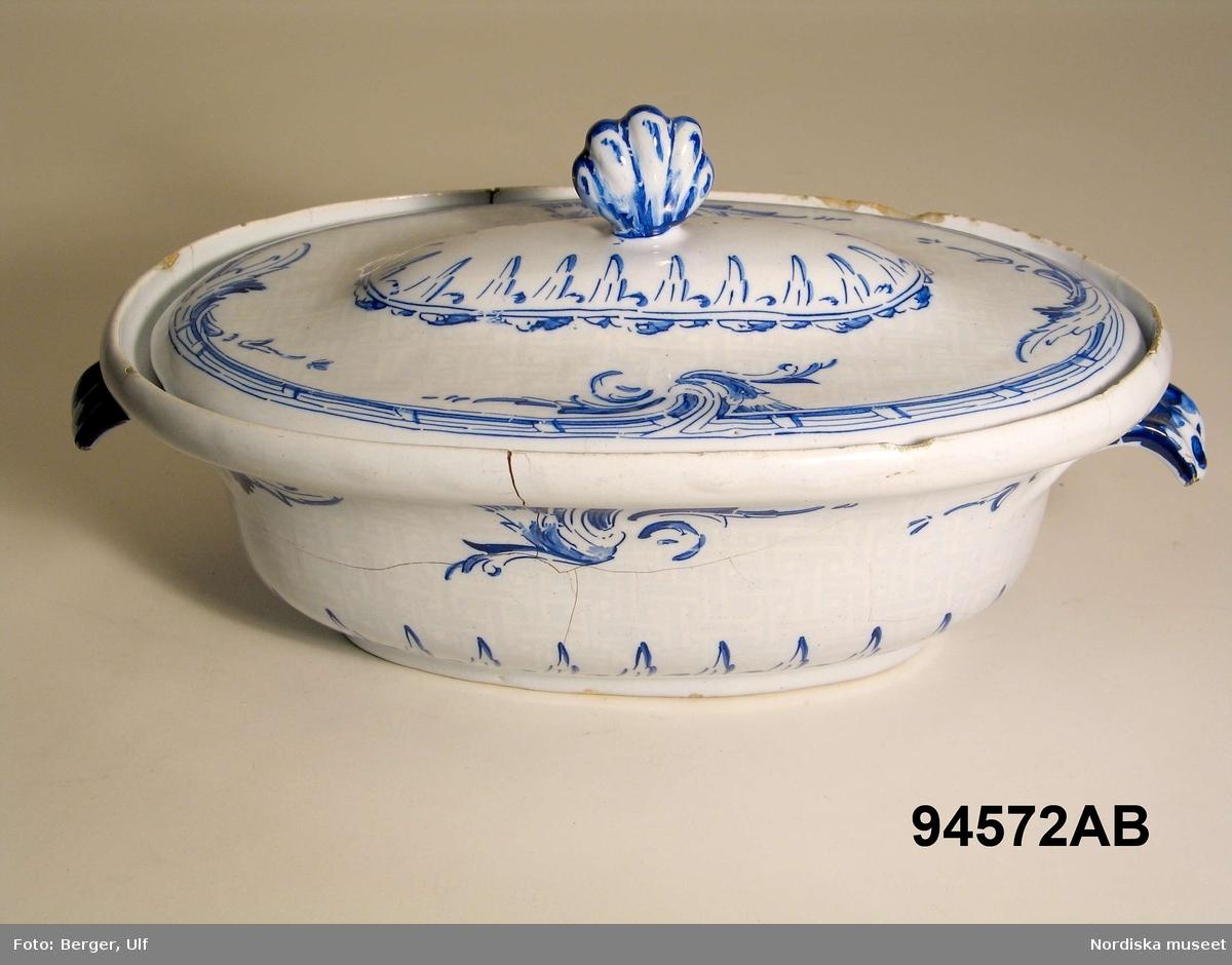 """Katalogkort:  """"Karott med lock och fat; fajans, målad dekor i blått. Oval svängd form med två handtag och svagt kupigt lock; fatet ovalt med kanten i flera pass; dekor. som no 74458 a -  bottnen m. flätmönster i 'sopra bianco'. Sign. i blått: Fatet: Stockholm 14/12 1757 8 sk A.  Karotten: Stock 30/7 1759 C E."""" /Upmark 1903  a= karott, b= lock, c= fat"""