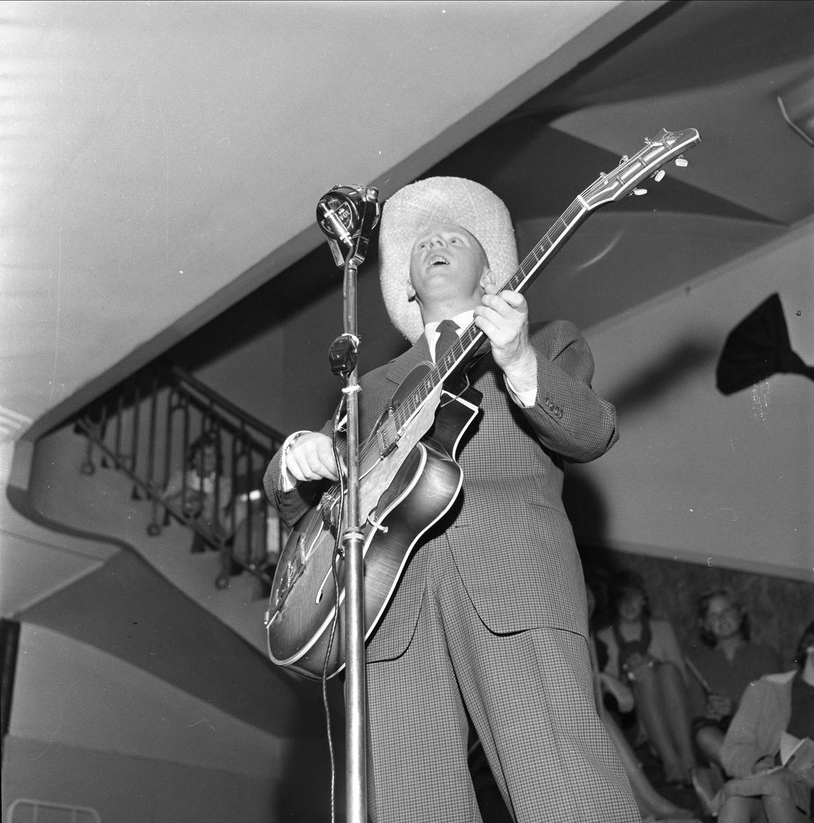 Arne Bendiksen synger og spiller. Moteoppvisning i varehuset Steen & Strøm, Kongens gate 23, Oslo, 28.10.1959.