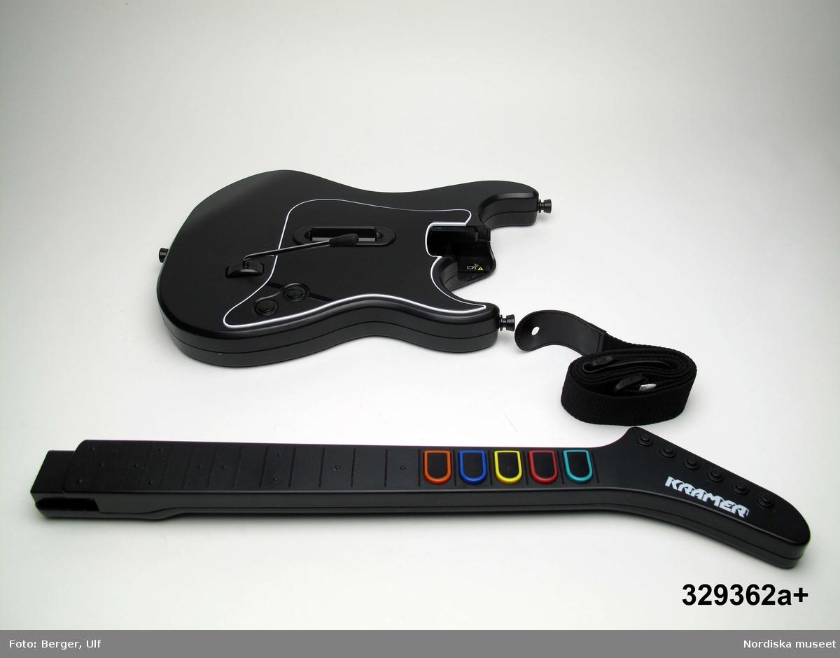 """TV-spelet """"Guitar Hero III Legends of Rock"""" med förpackning.  a+) Elgitarr med avtagbar hals, av svart plast, svart axelrem av syntettextil med konstläder (plast) och plastöglor. b+) 2 ark med klisterbilder att fästa på gitarren c) Broschyr med instruktioner om funktion och säkerhet på flera olika språk. d) Fodral av blå plast med inplastat omslag av papper med text. På framsidan """"Playstation 2 / Guitarr Hero III LEGENDS of ROCK"""" och bild på hårdrockare. Baksidan bl.a. """"SLÄPP LOSS DIN INRE ROCKLEGEND / Över 70 rockiga låtar."""". e) CD-skiva med programvara (förvarad i fodral d). f) Instruktionsbok på de nordiska spårken (förvarad i fodral d)  g+) Förpackning av papp. Ytterfodral med text och bilder. Inre lådan med inredning för de olika delarna.   Tv-spelet är avsett för spelplattformen Playstation 2, vilket är en vanlig spelplattform. Spelet går ut på att det spelas upp en låt (man väljer själv låt och nivå) och ska sedan försöka spela på gitarren genom att trycka på knapparna och på så vis lyckas spela samma ton som musiken spelar samtidigt.  Vid förvärvet avlägsnades plastpåsar som del av a och b låg i, samt två 1.5volts-batterier av märket Duracell som låg i gitarren, då de ej bedömdes möjliga att spara. Även fyra papperspåsar med Silicagel (för att hindra att fukt skadar elektronik mm) togs bort.  Nyinköp den 2008-02-20 för att rekonstruera julkklappsönskemål julen 2007 från Erik Thomelius född 1999, Vaxholm. Inköpt av Nordiska museet för 439 kr. Ingår i projektet """"Barn tar plats"""". Se dokumentation i arkivet D455. /Ulf Hamilton 2008-05-27"""