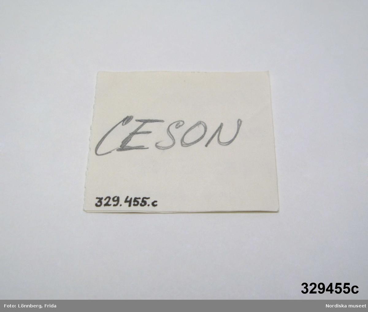 """Två små guldringar och etikett. a) Öppen ring av guldtråd, oval, stämplad """"K & EC - tre kronor - 18 K."""". Längd 0,5 cm. b) Öppen ring, ostämplad. Längd 0,5 cm.  c) Etikett av papper, dubbelvikt. Text på framsidan: """"Provöglor till oval komb K & EC - tre kronor - 18 K  0,8 mm kontroll 1 mm"""", text på baksidan """"CESON"""". Ur ask 329.449a. /2007-03-05 Heidi Henriksson"""