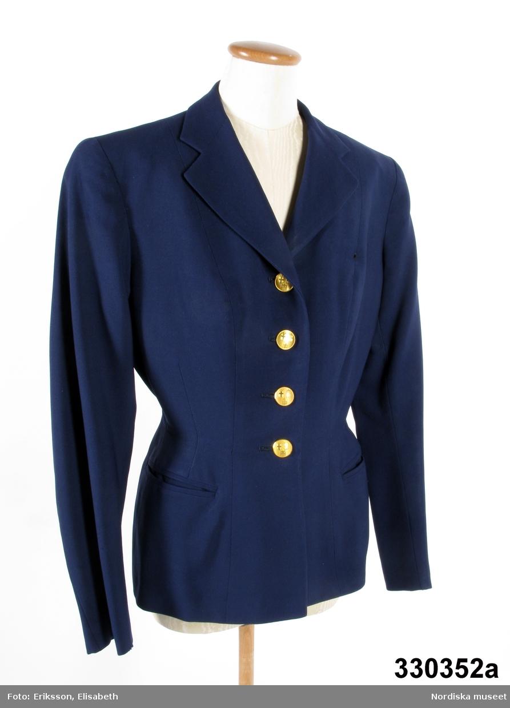 """Jacka till flygvärdinneuniform, SAS, 1948 års modell. Mörkblått ylletyg i panamaväv. Sommaruniform.Skräddad, välsittande, enkelknäppt kavajmodell med kraftigt insvängd midja. Lång tvåsömsärm, inskurna fickor å varje sida i höfthöjd. Framstycken med delningssömmar och insyningar mot fickor. Sidstycken. Bakstycke med mittsöm. Fodrad med mörkblått siden. Flera lagningar. Vidsydd tygetikett """"Mac Scott"""" samt hank för upphängning märkt """"MAC SCOTT"""". Fyra fastsydda mässingsknappar med SAS emblem. Märke sk """"vinge"""" fastsatt med skruv och plåt å vänster framstycke i brösthöjd.  /Ingrid Roos 2010-04-26"""