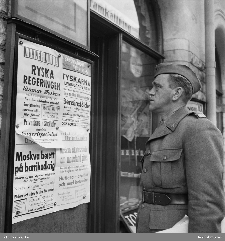 Författaren Wilhelm Moberg läser löpsedlar om kriget.