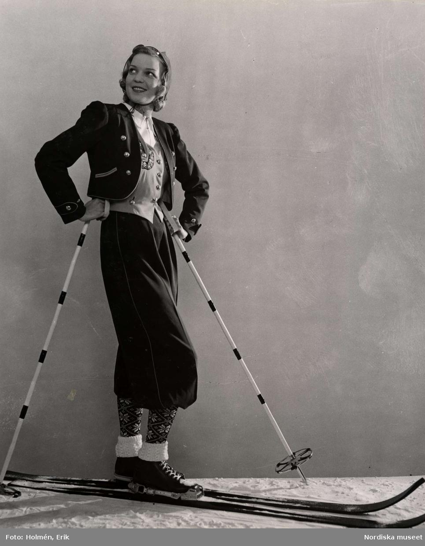 Vinter och friluftsmode. En kvinnlig modell iklädd skidkläder står och poserar på ett par skidor. Nordiska Kompaniet.