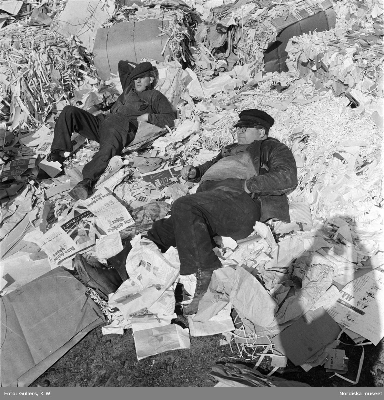 Stuveriarbetare i Stockholm tar en paus bland trasiga pappersbalar