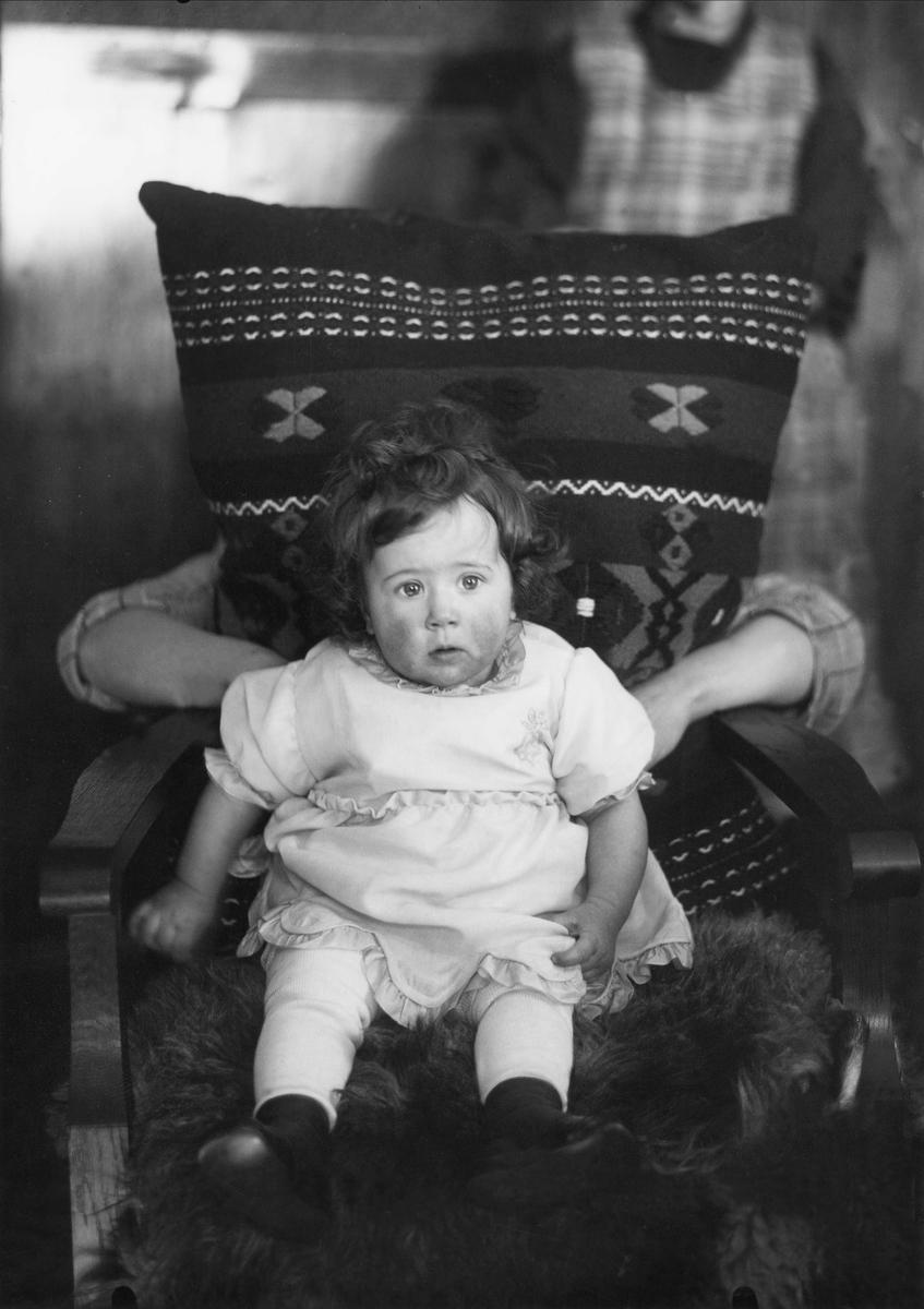 """Anna-Britta."""" Ett litet barn i en stol"""