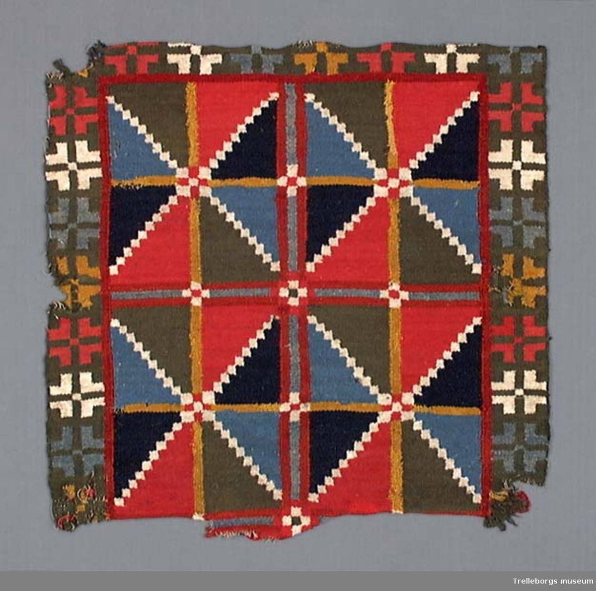 Stolajynne, röllakan, röd, blå, vit, m.fl. färger. Vävd i Klörup i slutet av 1700-talet. Vävnaden består av 4 stora rutor, vardera indelade i 8 fält, gula linjer horisontalt och vertikalt, samt rutor i vitt diagonalt. Dessa triangelformade fält är dels blå och gröna, dels ljusröda och mörkblå. Dessa rutor förekommer i vävnader från Luggude härad liksom de klara färgerna. De förekommer också i Vemmenhögs hd. men då har den blå färgen kommit in som i denna vävnad.Denna typ av ruta som utvecklades till stjärna förekommer endast på äldre vävnader och försvann under 1800-talet. På denna vävnad bildar de huvudmönster, vanligare är att de är utfyllnad. Bården utmed 3 sidor har grönt som bottenfärg och i denna små vinklade stjärnor i ljusblått, vitt, skärt, gult. De förekommer i NV Skåne och södra Halland.