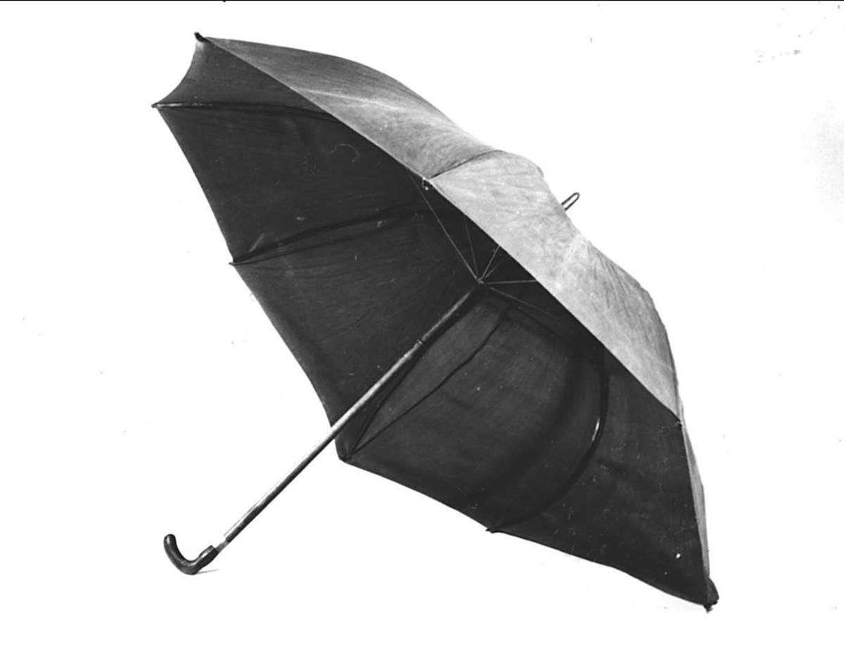 Paraply av brun bomullskypert, skott med läder vid stången. Stång av trä, beslag av mässing. Spröt av mässing och trä. Krycka av horn med graverad dekor.
