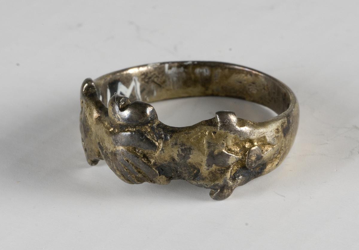 Ring av av förgyllt silver. Två händer och växtornament.
