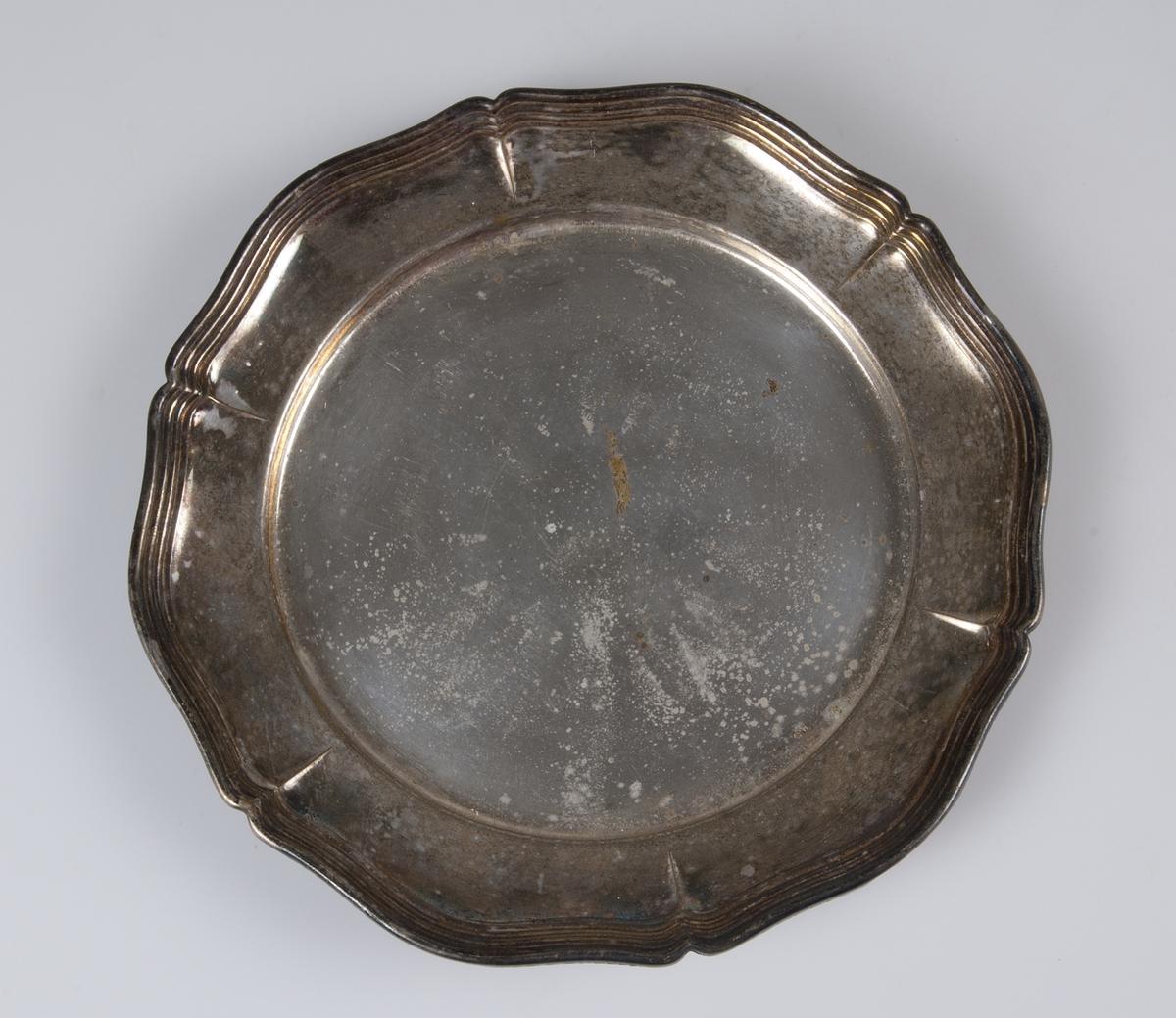 Smörassiett med skål av glas (se UM09421a), samt fat av nysilver med vågig kant. Saknar stämplar.