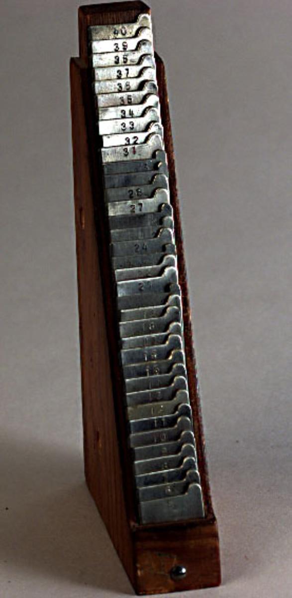 Sättlinjer i träställ. Sättlinjerna är metallplattor av svagt gulaktig metall  med utskjutande hörn, i överkanten stämplade med nummer 5 - 40 samt stämplade AWE. Sitter tätt i trekantigt träställ, nr 5 underst. Två hål genom det trekantiga trästället för fastsättning .