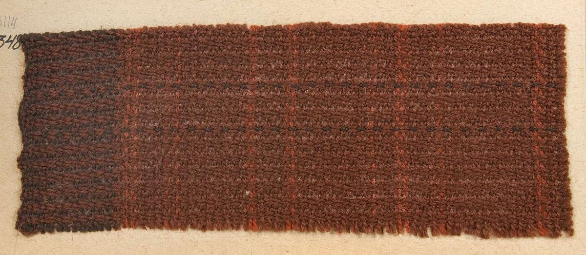 """Vävprov ämnat för draperityg vävt med ullgarn i rödbrunt. Vävprovet har nummer """"B-1348""""."""