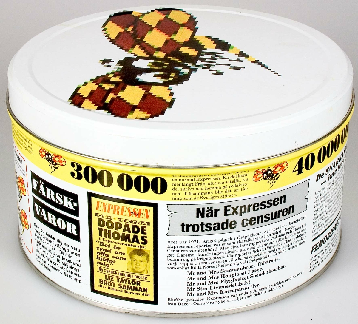 Kakförpackning av järnplåt. Tryckt dekor: vit bottenfärg. På locket tidningen Expressens logotype i svart, brunt och gult. På burken illustrationer och texter om tidningen Expressen.