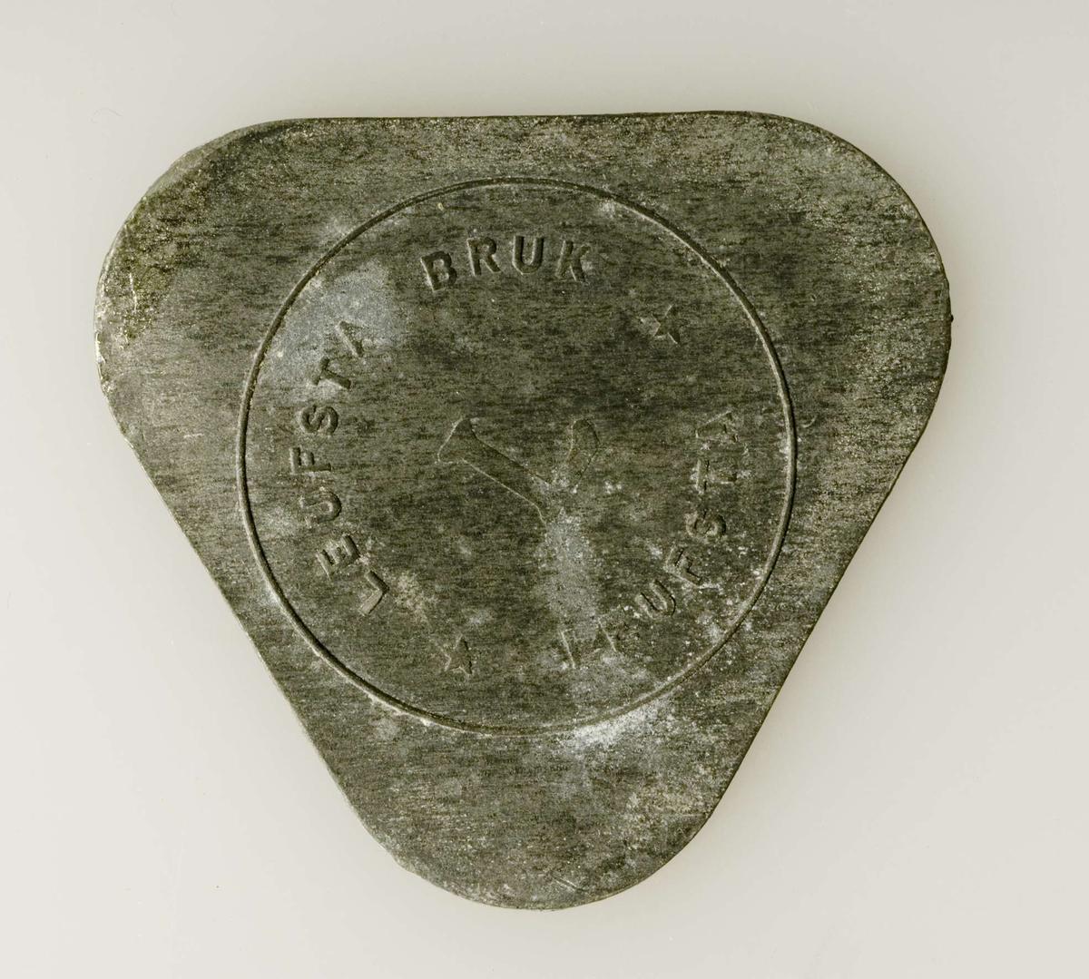 Pollett av tennliknande metall, trekantig med rundade hörn. Lövstabruks stämpel i relief.