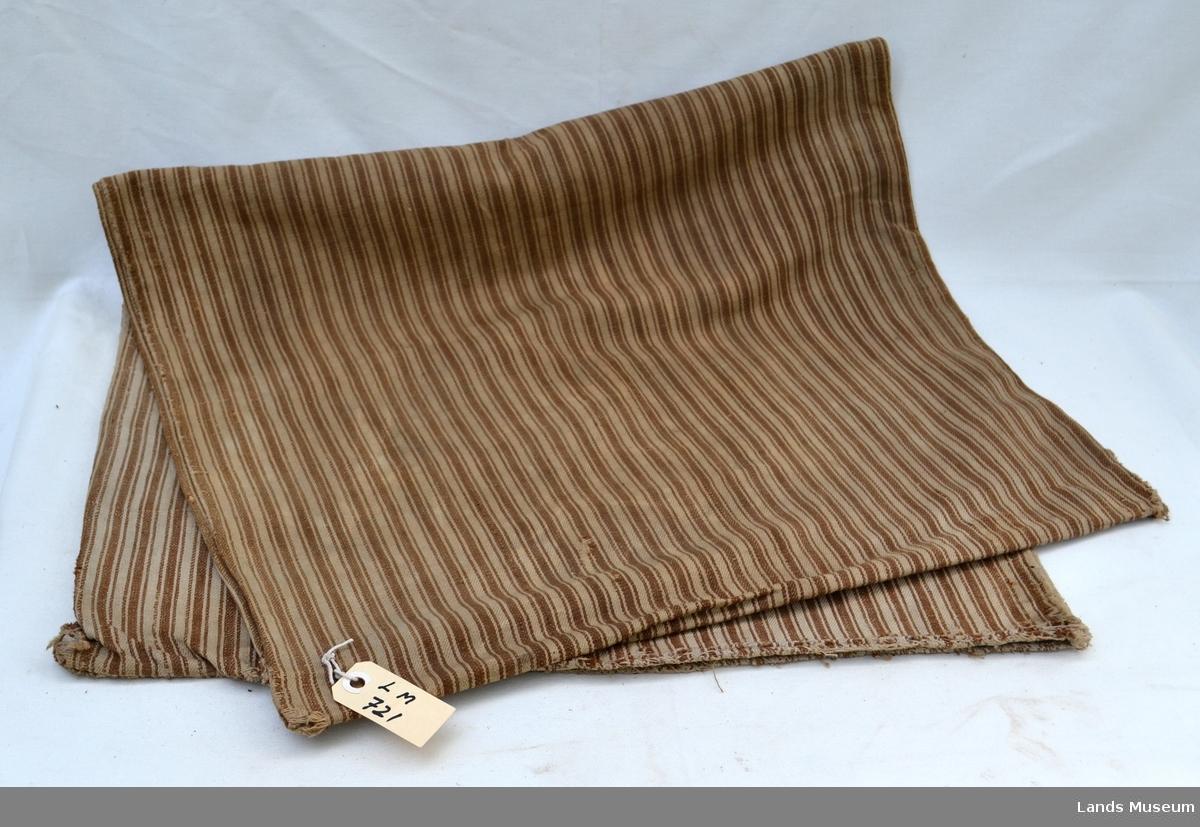 Putevar, avlangt med striper i brunt og kvitt.