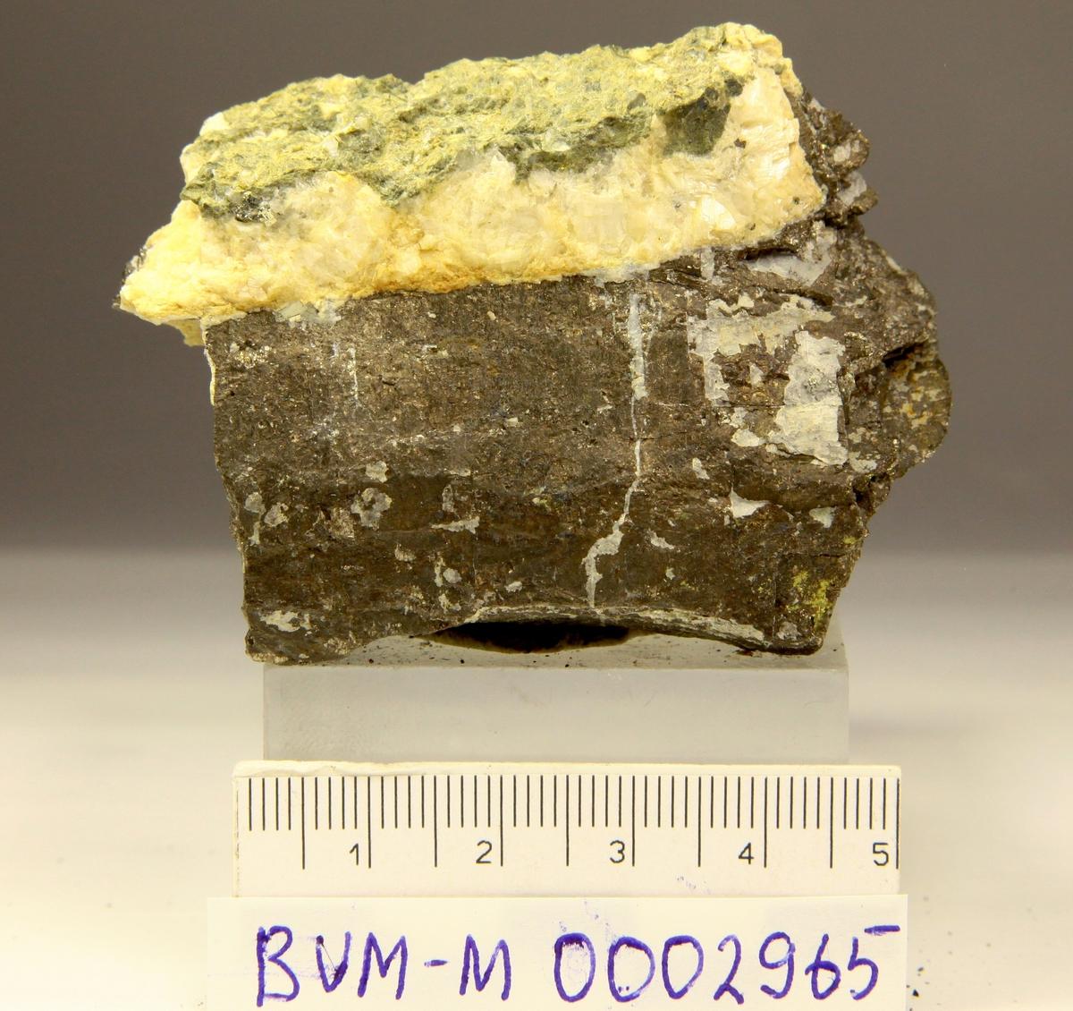 Grovkornet pyrrhotitt, mulig 2 krystallflater, med hvit karbonat. Mannsfjellstunnelen, E39, Skaun.