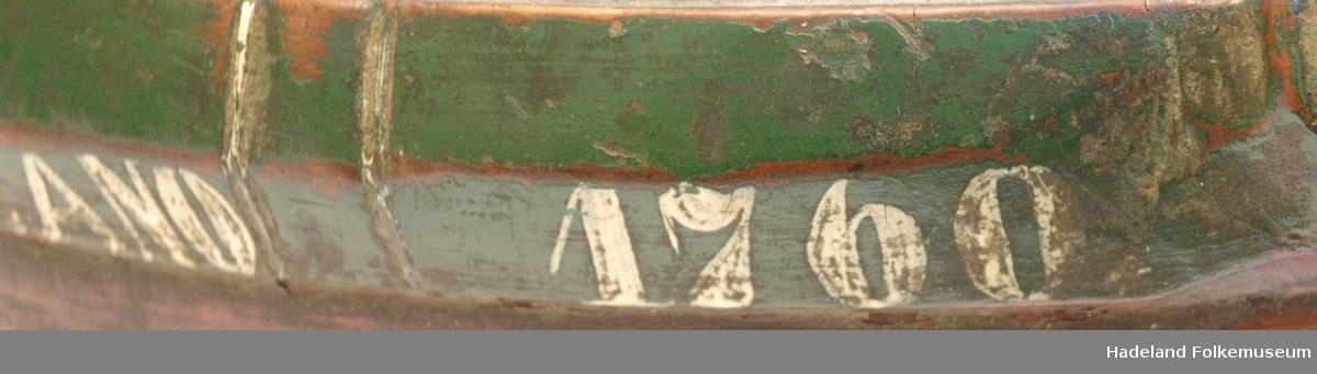 Trebolle med nebb/tut på ene siden og øre/håndtak på den andre siden. Rødmalt, med grønt felt øverst. Sekundært montert øyekrok i korpus.
