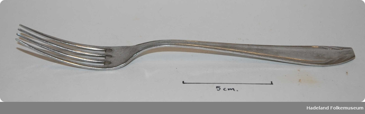 4 tenner, jevnt avsmalende skaft med mønster som blader/ eller en vifte som bretter seg innover skaftets ende. Dekoren er på begge sider. Merket framme ved tennene .