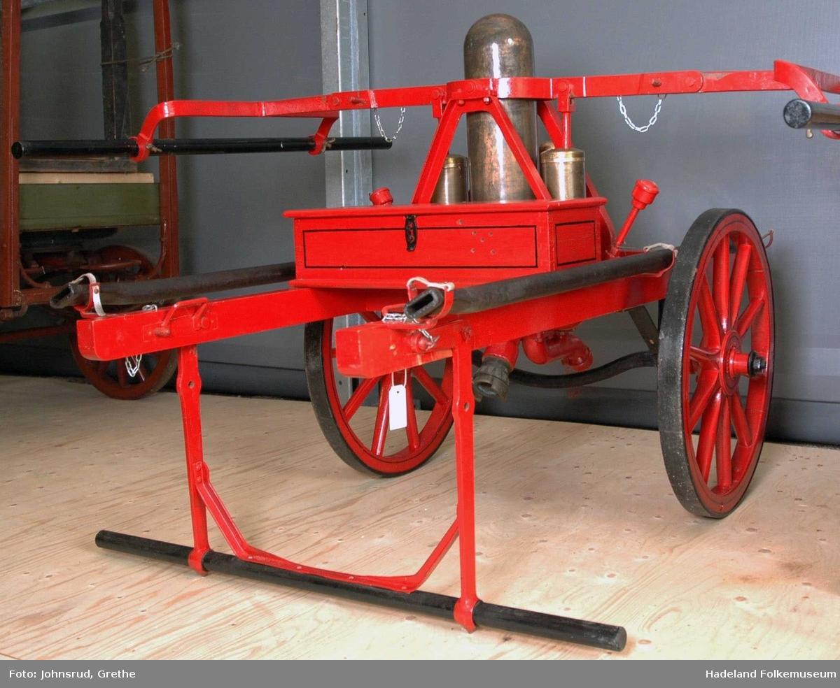 Brannpumpe for fire personer. Laget av tre med jernbeslag og pumpesylindre av messing. Rødmalt treverk med svarte striper.