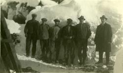 Fem arbeidere og en mann med dress og slips står oppstilt på