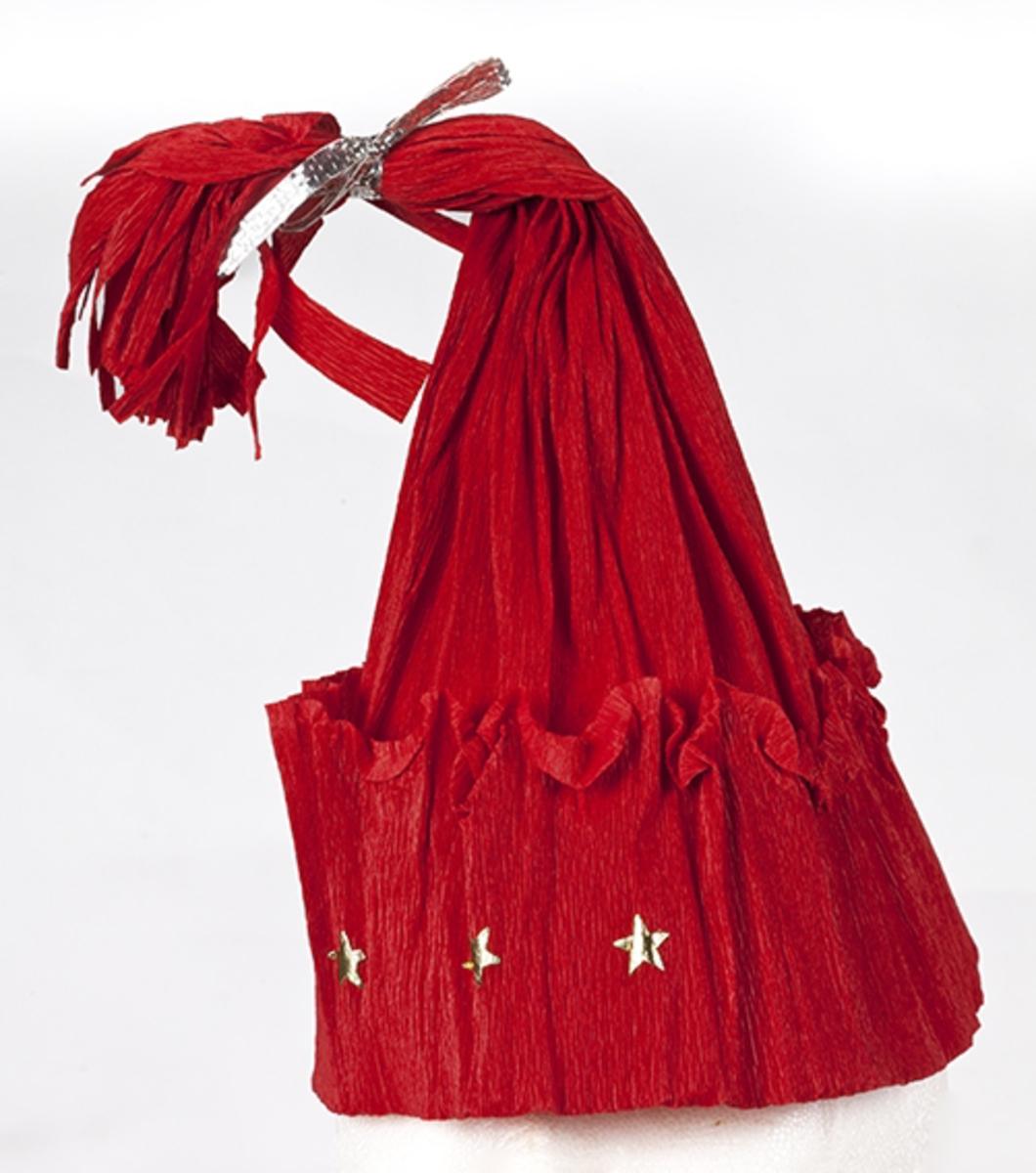 """Laget av kreppapir, formet som topplue med dusk. Dekorert med tre gullstjerner og sølvbånd rundt dusken. """"Nisselue"""".Antatt 1950-tall."""