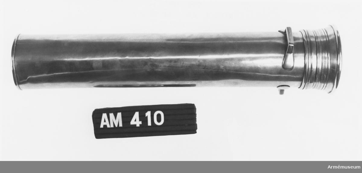 Samhörande nr är 294-299, 321-350, 400-448 (410-411). Mässingfodral t trumpinnar, Danmark. Nyttjades i danska hären 1810-1851. Utgick enl. armébefalig 1851-02-03. Gåva av danske CA generallöjtnant Otto Blixenkrone-Moeller vid hans besök i Sverige sep 1972. Locket är fäst vid burken med ett gångjärn i mässing. Två st. handtag sitter strax under locket, även de i mässing. På danska: Messinghylster till trommestikker.