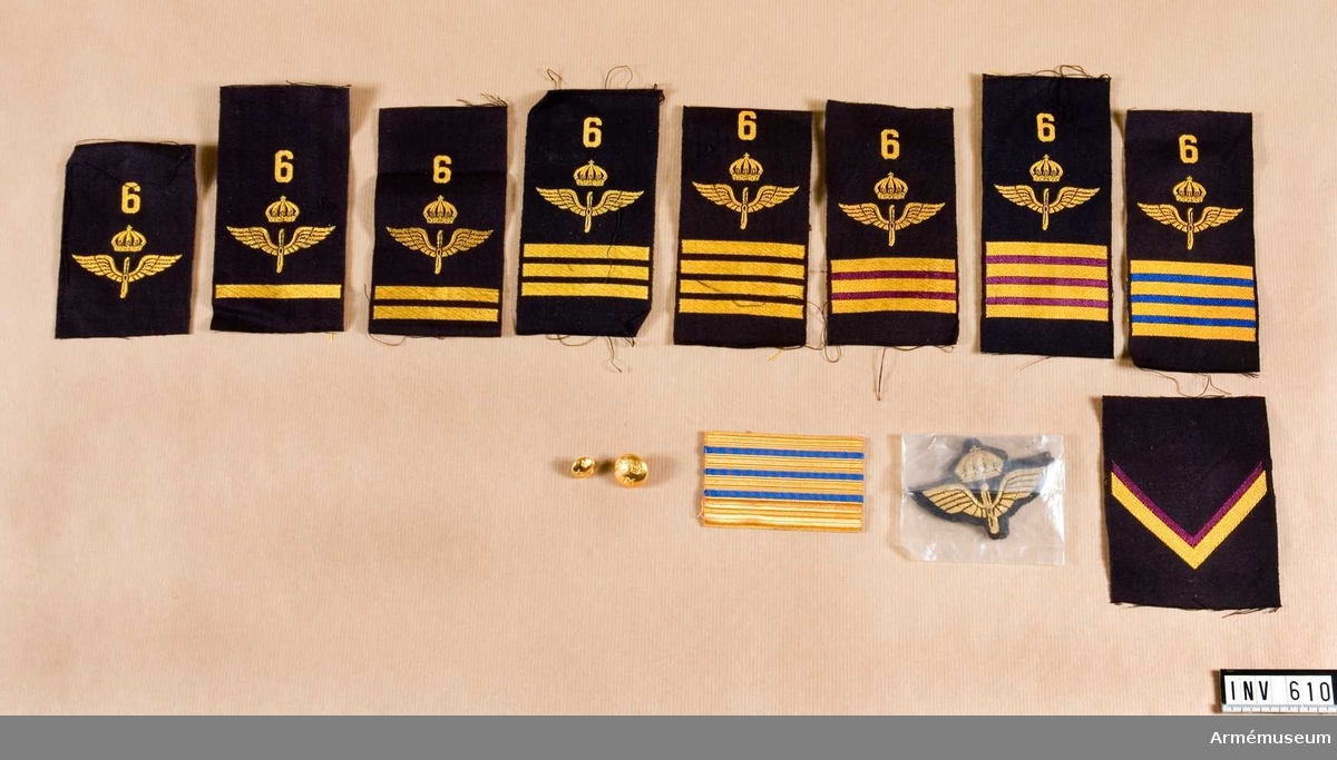 Låda med flygemblem. Gradbeteckning på axelhylsor m/1951 för överfurir teknisk  personal, flottiljpolispersonal och furir teknisk personal. Kläde i färg anbringas mellan strecken, alltså i dagern, enligt följande: tekniker = violett, flottiljpolis = ljusblått. Gradbeteckning på axelhylsor m/1958 för överfurir flottiljpolispersonal och teknisk personal, furir teknisk  personal, korpral och menig. Beträffande färgen se ovan. Överfurir motsvarar fyra kortare streck 4 mm breda, furir tre kortare streck 4 m breda och korpral två streck 4 mm breda. Gradbeteckning på armar m/1930 för överfurir (fyra större streck), furir (tre streck), korpral (två större streck) och vice korpral (två större streck) och menig (utan beteckning). Knappar m/1930, större och mindre.