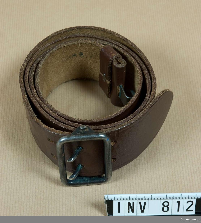 Samhörande nr är 805, 810-812. Livrem m/1939, manskap. Tillåten modell för manskap m:1939. Remmen har ett enkelt spänne i stål med två torn och en sölja i läder.