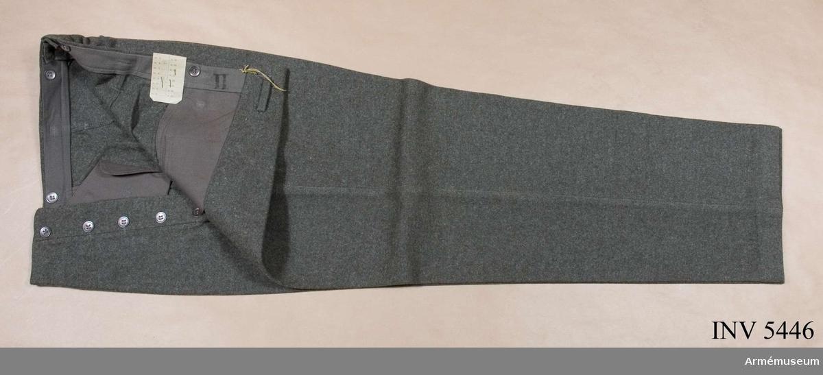 """Stl 104 L. Gråbrungrön ylletyg. Raka ben och julpknäppning. Sidfickor och en bakficka. Hällor i linningen, knappar för  hängslen på insidan. I linningen etikett """"CBV"""" = Försvarets fabriksverk, centrala beklädnadsverkstäderna, Karlskrona. Bäres till vapenrock m/1939."""