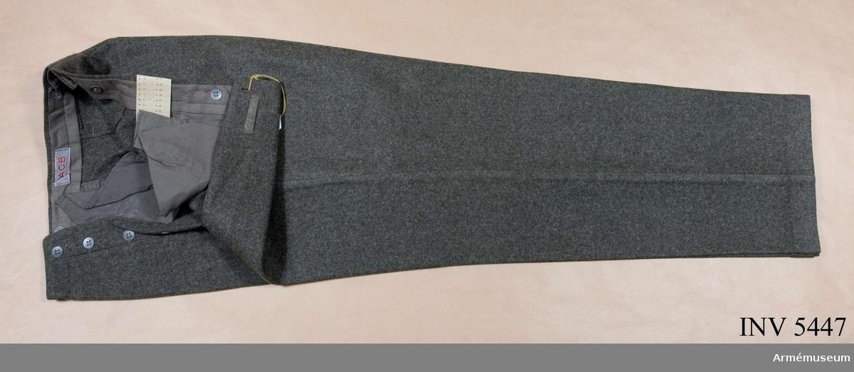 """Ylle.Stl 104 L. Gråbrungrön ylletyg. Raka ben och julpknäppning. Sidfickor och en bakficka. Hällor i linningen, knappar för  hängslen på insidan. I linningen etikett """"CBV"""" = Försvarets fabriksverk, centrala beklädnadsverkstäderna, Karlskrona. Bäres till vapenrock m/1939."""
