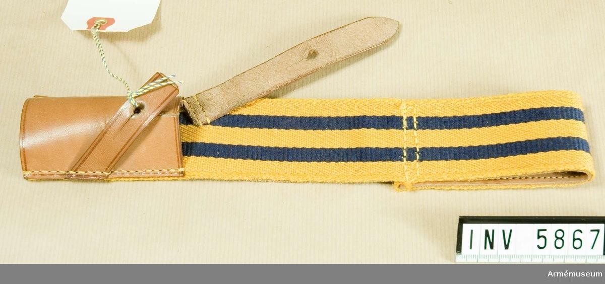Samhörande gåva: 5828-5899 + 6000-6099 + 6200-6205.Hylsa m/1931 till bajonettbalja för alla truppslag.Gott skick X2. Längd 270 mm, bredd 45 mm. Färg gul C, blå M.Fastställt genom go 21 november 1931 nr 2506. Hylsan är av kypertvävt redgarn i gult med två mörblå ripsvävda ränder,  vardera 7 mm breda. Bandet är fodrat med ljust läder och upptill vikt dubbelt till en tunnel, genom vilken man skall dra  skärpet m/1910-1931. Hylsan för bajonetten är av ljust läder  och sitter nedtill på rätsidan. Två snedställda läderremmar skall knäppas mot bajonetten.