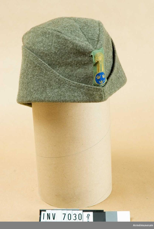 Mjuk båtmössa tillverkad av gråbrungrönt ylletyg, kommiss, samt försedd med svettrem och uppslag, vilka senare kan vikas ned till skydd för öron och nacke. Kan även användas som hjälmskydd. Agraffen m/1960, såväl knapp som galon och kokard, är av vävnad.Källa Svenska försvarets mösmärken 1977. Wilhelm Wahrenberg. Sidan 25.