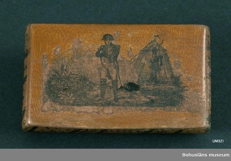 Ur handskrivna katalogen 1957-1958: Snusdosa Mått: 8,5 x 5 x 1,8 cm; av trä m. lock på gångjärn; på locket bild av Napoleon I i fält; tuschdekor å öve. sidor. Ngt skad.   Lappkatalog: 95