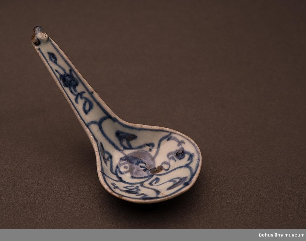 Ur handskrivna katalogen 1957-1958: Matsked L.10,9. Br. 5,2. Ljust vitblå botten med blått mönster. Något skadad. En spricka.  Lappkatalog: 62