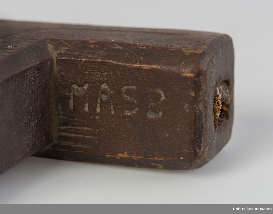 """Ur handskrivna katalogen 1957-1958: Borrvind, skulpterad, Uddevalla. L. 35 cm; helt av trä; klumpig, m. utskuren dekor på alla sidor """"MASB""""; svarvad tryckplatta. Hel."""