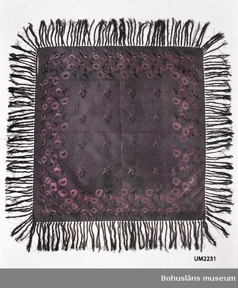 Användningstid 1830-1890, förmodad. 503 Kön KVINNA  Kvadratisk jacquardvävd sidenschalett i svart och rödlila, med spridda löv i mittspegeln och en bård med naturalistiska blommor och blad. Påknutna ca 13 cm långa fransar i svart och ett fåtal rödlila trådar. Tillverkningstiden uppskattad med mönstret som utgångspunkt. På 1830-40-talen under nyrokokon kom naturalistiska blommönster. På 1880-talet blev nyrokokoinspirerade mönster åter populära. Möjligen pekar den skarpa/mörka färgen mot att schaletten är från nyrokokons andra blomstringstid. Men det faktum att schaletten är handfållad pekar mot en datering till innan 1860-talet, då symaskinen blev mer vanlig. Brytskador längs gamla vikningar. Bristningar, speciellt nära ett av hörnen. Många ytterst små hål, troligen nålhål från användningen. Skör. Svagt synliga fläckar.  Litt; Håkansson, Elin, Sidenhalsdukens bruk och tillverkning ur Sörmlandsbygden 1933.  Lindvall-Nordin, Christina, Mossrosor och hjärtblomster ur Kulturens årsbok 1969, Lund.  Wulfcrona-Dagel, Marie Louise, Schaletter och halskläden i Nordiska museet vävda hos K A Almgrens sidenväveri i Stockholm, uppsats för fortsättningskurs i etnologi, Stockholm 1979.  Ur handskrivna katalogen 1957-1958: Silkeduk, lila. Mått c:a 73 x 71 cm. Blomsterbroderier i lila o svart. Försedd m. frans. Duken något trasig och blekt.
