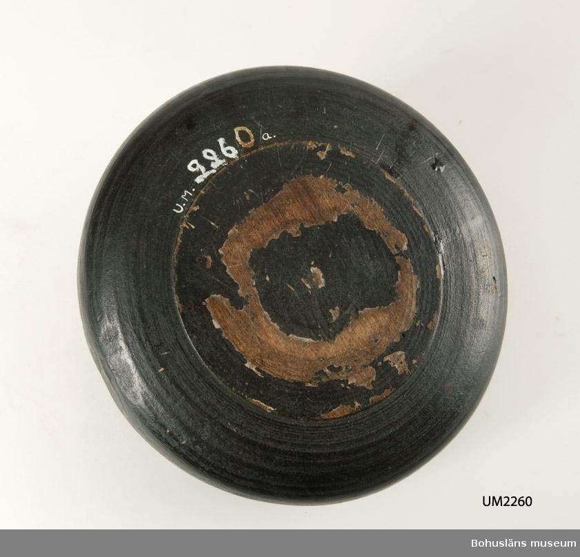 """Rund, svarvad med lock. Locket har en rektangulär knopp mittpå. På en av knoppens sidor finns ägarinitialerna """"OMS"""" och på andra årtalet """"1844"""" skrivet i rött. Målad i mörkt grönt. Rinnmärken efter sekundär ytbehandling. Sprucken i nederdelens kant.  Ur handskrivna katalogen 1957-1958: Grönmålad träask m. CMS 1844 Asken a) största D. 21; H. c:a 7 cm; locket b) största D. 18,2 cm. Svarvad, en spricka i asken."""
