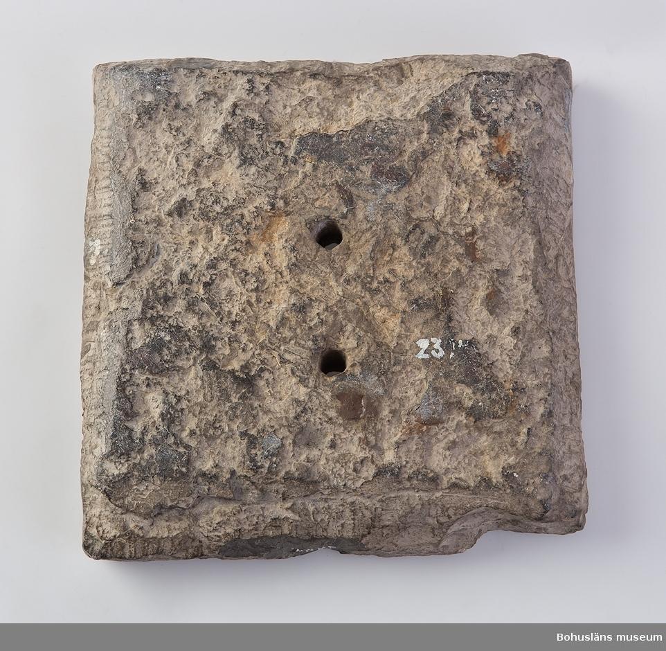 """Ur handskrivna katalogen 1957-1958: Solur """"1704"""" Mått: 17,3 x 17,5 x 3,8 cm; av kalksten(?); 3 hål på framsidan; under """"1704"""" : """" F. S. M. L."""". Helt.  Litteratur: Kristiansson, Sten: Glimtar från Uddevalla museum. Tidmätare. Se biblioteket, Ncbk: Uddevalla."""