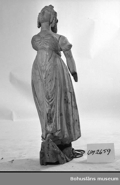 """Föremålet visas i basutställningen Uddevalla genom tiderna, Bohusläns museum, Uddevalla.  Galjonsfigur från 1800-talets början. Kvinnofigur i empirklänning. Snäckor pryder håret som är arrangerat i en konstfull uppsättning med korkskruvslockar. Vitmålad figur. Höger arm liksom vänster hand saknas. Förgyllning i klänningens nederkant. Svartmålad volutslinga som placerats som fundament. Figuren bär spår av en tidigare ljusgrå målning. Sockeln har spår av förgyllning. Lagningar, en infälld bit vid mellangärdet och en på främre benet. Stora torrsprickor. Den högra armen saknas samt den vänstra handen. Förvärvsomständigheter okända.  Ur handskrivna katalogen 1957-1958: Galionsbild fr. o. 1800. H. c:a 1,22 m. Br. c:a 0,38 m. Kvinnofigur i veckrik klädnad, stående på en rocailleliknande bas. Trä, vitmålat. H. armen borta, v. (Hand saknas) lagad. Sprickor o små hål. Bilden lagad på ett flertal ställen. Färgen avflagad.  Lappkatalog: 46  Litteratur: Hallén, Tore, Rüster, Reijo, """"Galjonsbilder"""", Rabén & Sjögren, 1975. Vissa sidor finns kopierade, se Bilagepärm UM2659. Kristiansson, Sten: Uddevalla stads historia II. 1953, s. 503. Bilagepärm: """"Vill du köpa en fågelskrämma? Would you like to buy a scarecrow?"""" Historien om galjonsfiguren Jenny Lind - The story about the figurehead of Jenny Lind. Skrift som troligen är författad av Karl-Eric Svärdskog, Göteborg år 1997 i samband med Tall Ships' Race i Göteborg  i augusti samma år. 16 s."""