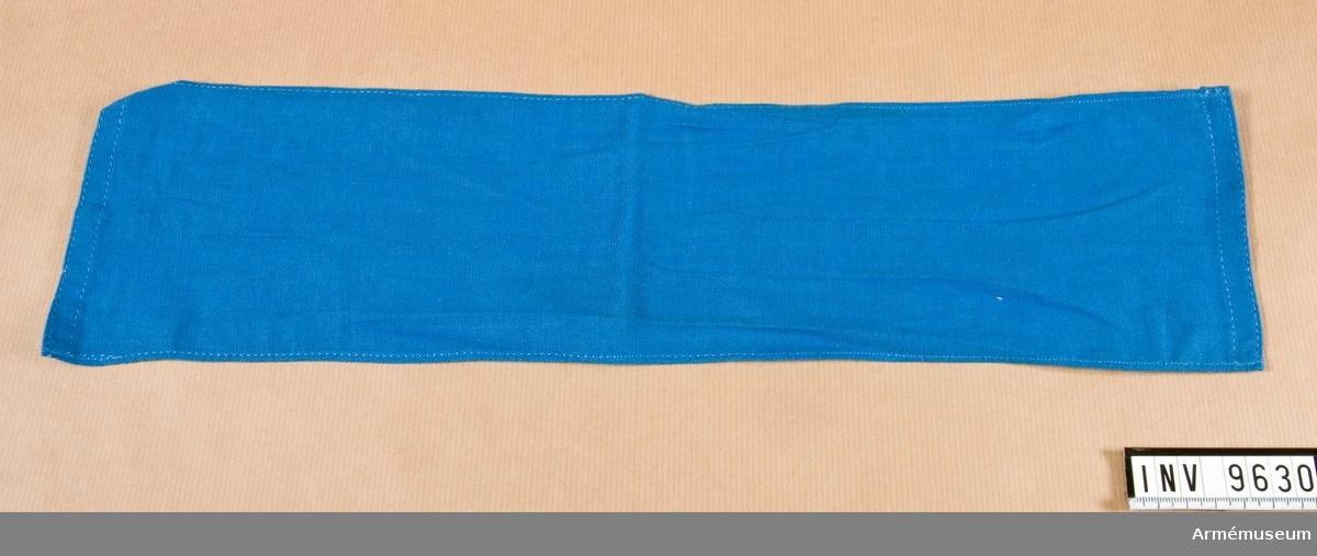 Armbindel av blått bomullstyg. Användes vid fälttjänstgöring och betecknar presstjänst.  Samhörande nr är 9605-9650 + 9659-9666.