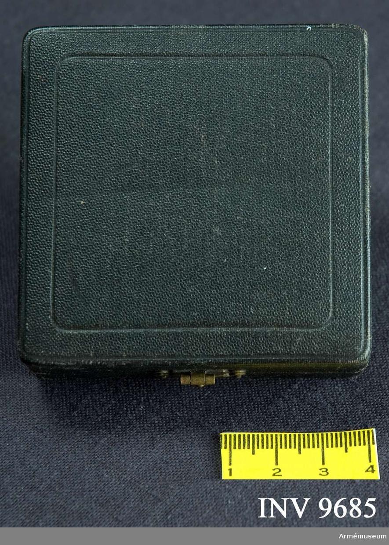 Samhörande nr är 9684-9685. Tillverkad av svart s k klot med uppfällbart lock och knäppe i gulmetall. Botten är klädd med lila sammet och locket med lila  siden i samma nyans. Minnesmedaljen förvaras i asken.