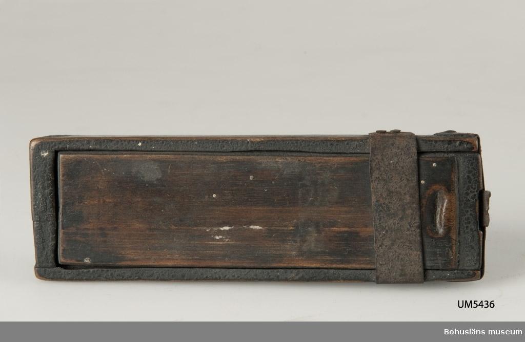 """Rektangulär låda med skjutlock upptill. Vid en av kortsidorna löper ett metallband runt kanten som förstärkning samt tvärsöver ovansidan. Locket har en spärr av metallplåt. Inuti ligger en vikt papperslapp med namnet """"Lundin"""" skrivet i bläck. Betsad. Har brännskador på kanterna.  Litt.; Gjaerder, Per, Esker og tiner, C. Huitfeldts förlag, Oslo, 1981, s. 48-50.  Ur handskrivna katalogen 1957-1958: Avlång träask m. skjutlock Mått: 13 x 4,4 x 2,3 cm; skoningar av järn; i locket b) spärr av järnplåt. Sprucken i ena ändan.  Lappkatalog: 84"""