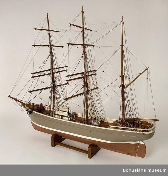 """Tremastade barkskeppet Elisabeth, Fiskebäckskil. Tillverkad av kapten John Emil Olsson (1880-1950), Fiskebäckskil på Skaftö i Lysekils kommun på 1940-talet. Trä, metall, lintråd.  Höjd 91 cm, längd 120 cm, kölens längd 87 cm, B 39 cm. Okänd skala. Blockmodell målad i grått och rött med vit vattenlinje. Stående och löpande rigg med utskurna block. Detaljrik modell med galjonsbild, däckshus, ratt, nakterhus, lastlucka, relingsgång, nagelbänkar, ankare, vinschar och spel, länspump, ventiler, lejdare och livbåtar. På akterspegeln står textat med svarta versaler: ELISABETH FRÅN FISKEBÄCKSKIL  Ur handskrivna katalogen 1957-1958: Barkskeppet """"Elisabeth"""", Fiskebäckskil. Kölens L. 87. Modell. föremålet helt. Från kapten Olssons saml., Fiskebäckskil.  För ytterligare information om förvärvet, se UM005807.  Föremålet presenterat på Bohusläns museums hemsida år 2009 - 2013, webbutställning """"John Emil Olsson Fiskebäckskils sjöfartsmuseum""""."""
