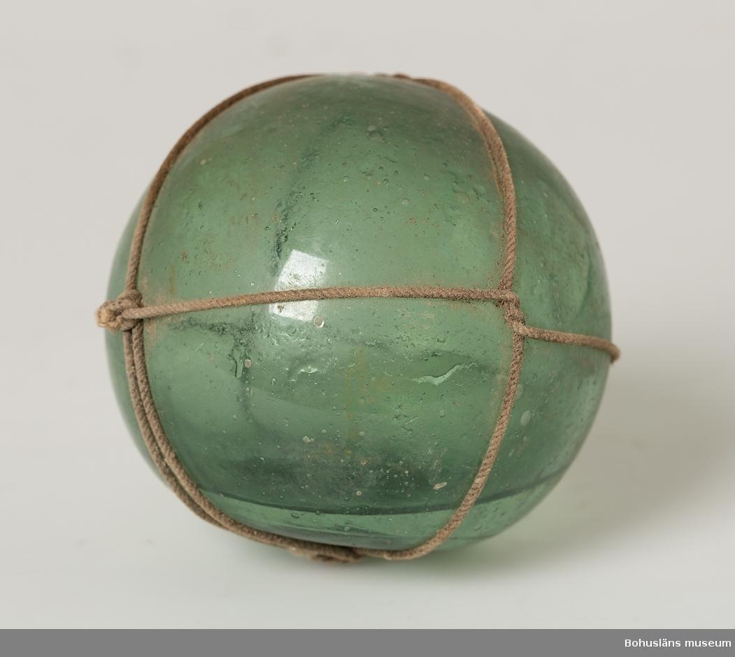 Grön glaskula. Omknuten med bomullssnöre. Puntelmärke. Spricka. Det är vatten inne i kulan.
