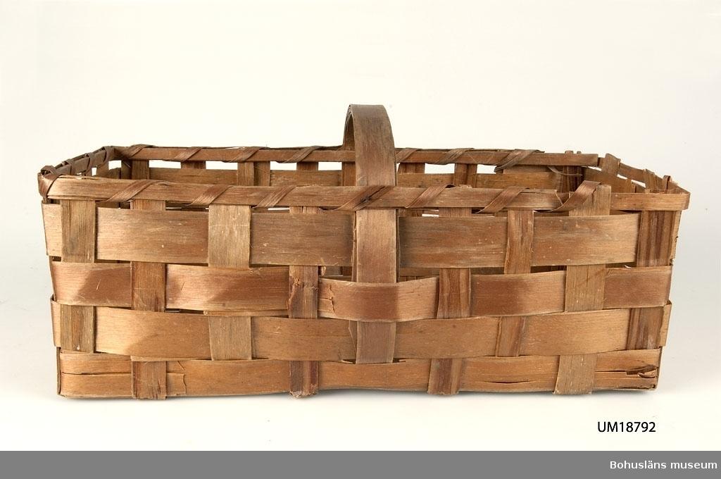 Korg i avlång modell av spånor med bärhandtag på tvären.