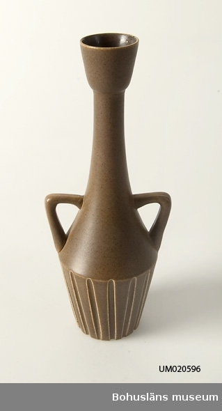 Brunglaserad,närmast amforliknande vas med räfflad nederdel. I botten märkt med inristad signatur och på vasens sida påklistrad firmaetikett från SYCO. Jfr. UM20597.