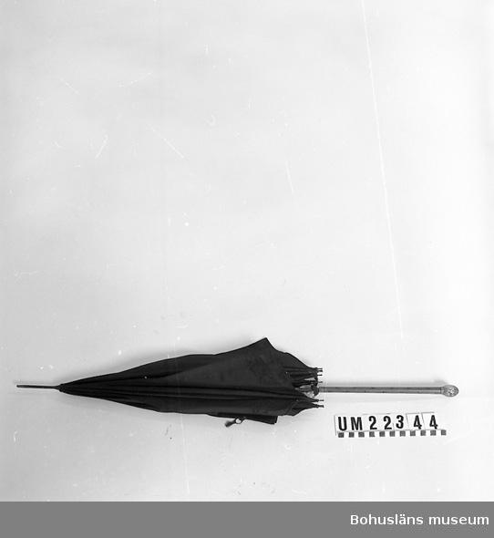 594 Landskap BOHUSLÄN  Paraplyn är av svart tyg, knoppen på handtaget är dekorerad med blommotiv och är av vit metall.  UMFF 101:1