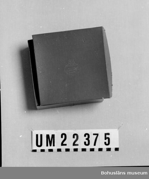 """594 Landskap BOHUSLÄN  Asken är röd, på locket finns Uddevalla stads vapen med text: """"Etabl.1879 Guldsmed J.A.Bokström Uddevalla"""".  UMFF 104:1"""