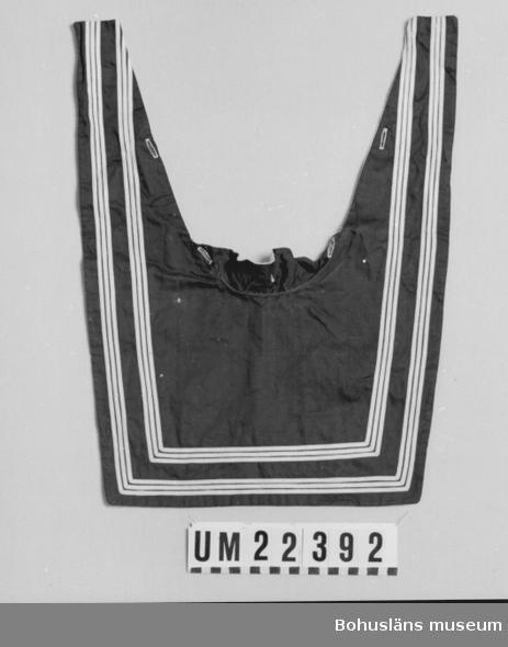 594 Landskap BOHUSLÄN  Översida av mörkblått tyg av bomull med sex vita ränder. Undersidan vitt. Fem st.knapphål.  UMFF 105:7