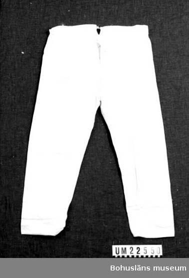 410 Mått/Vikt! BENV 19, BENL 67 CM 594 Landskap BOHUSLÄN  Vita långbyxor med sprund bak med snöre. Sprund också vid byxbenen. Gylf fram med två knapphål och en knapp. En ögla av vitt bomullssnöre i översta knapphålet.  UMFF 125:4