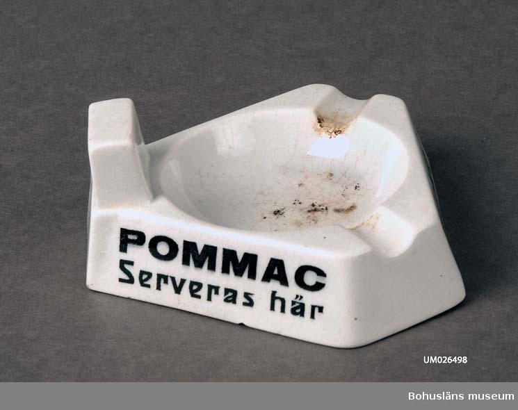 """Trekantig med kapade hörn. I ena hörnet är det plats för en tändsticksask.  Vit med svart text på sidorna: """"POMMAC Serveras här"""", """"Dricker Ni POMMAC"""" och """"POMMAC Smakar härligt"""". Stämplat i godset GÖTEBORG, 25, 2 och T. Med en tryckt svart stämpel under glasyren Göteborg (i skrivstil).  Tjära efter användning har valts att få finnas kvar.  Föremålet var tidigare katalogiserat och märkt under UM16636 liksom en såsskål, varpå detta föremål fick ett nytt nummer.  Litteratur: Göteborgs porslinsfabrik. Priskurant 1920. Priskurant öfver Göteborgs porslinsfabriks tillverkningar 1920."""